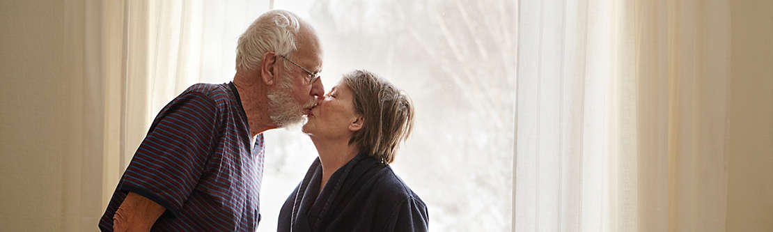 Senior couple kissing next to window
