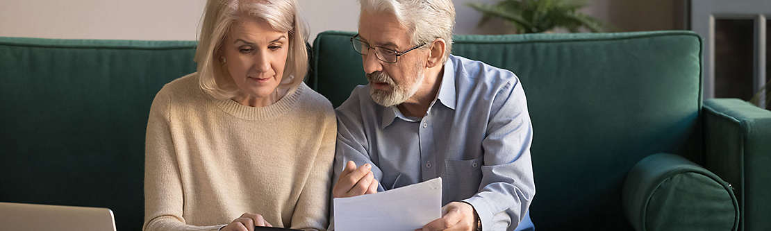 A mature couple siting on the couch looking a paperwork.