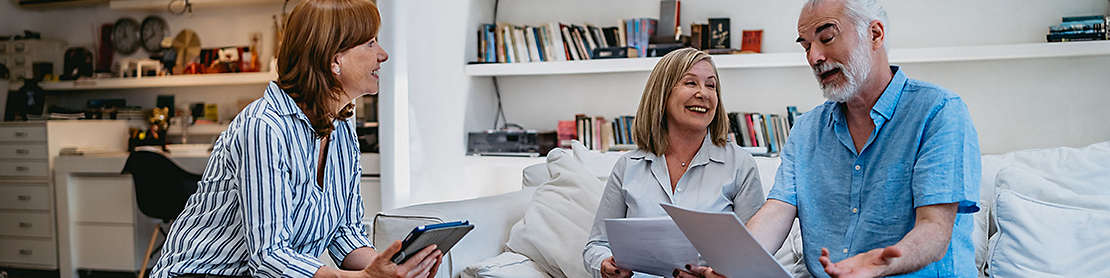 A mature couple at home discussing paperwork with an agent.