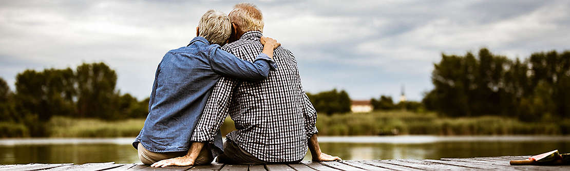 A mature couple outside sitting on a dock overlooking a lake.