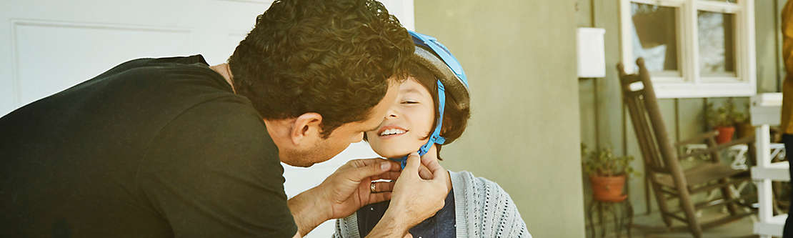 Father helping daughter buckle helmet before riding scooter