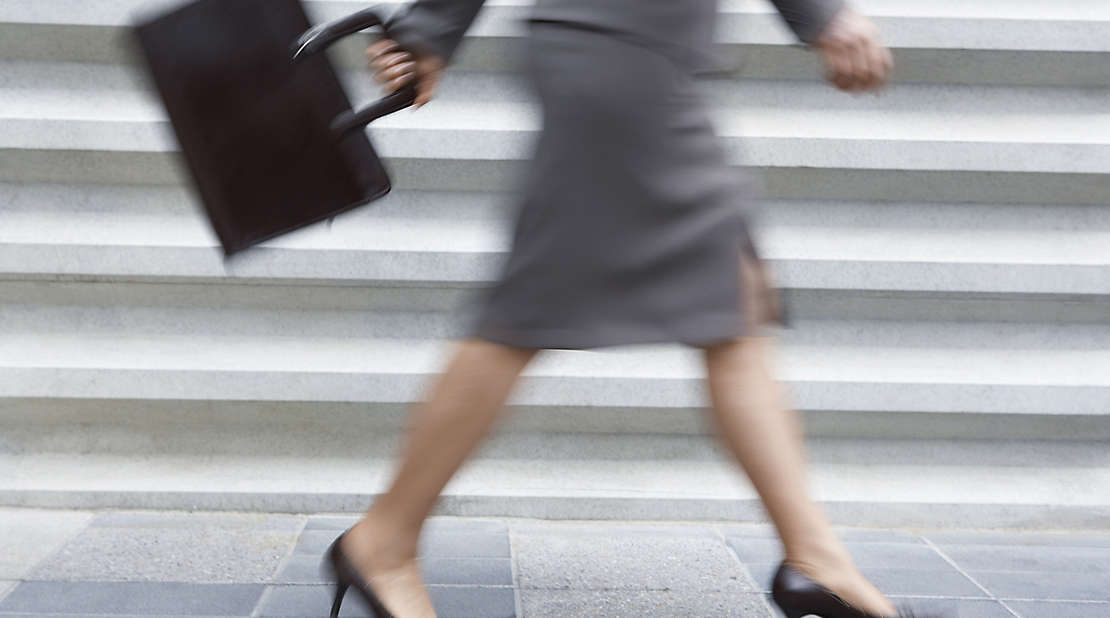 A working mother walking with a briefcase.