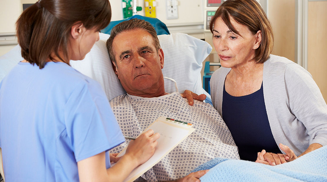man in hospital with nurse and spouse
