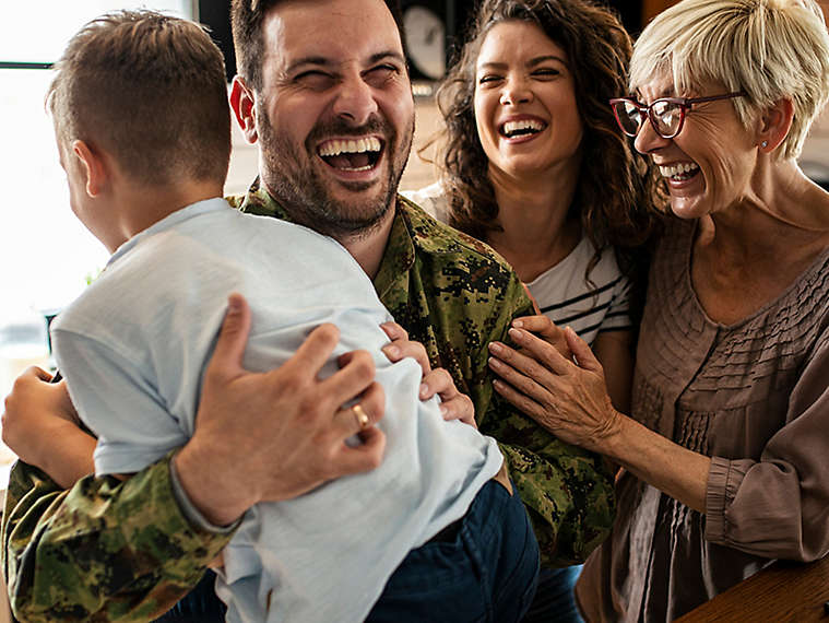 Family laughing together in their kitchen.