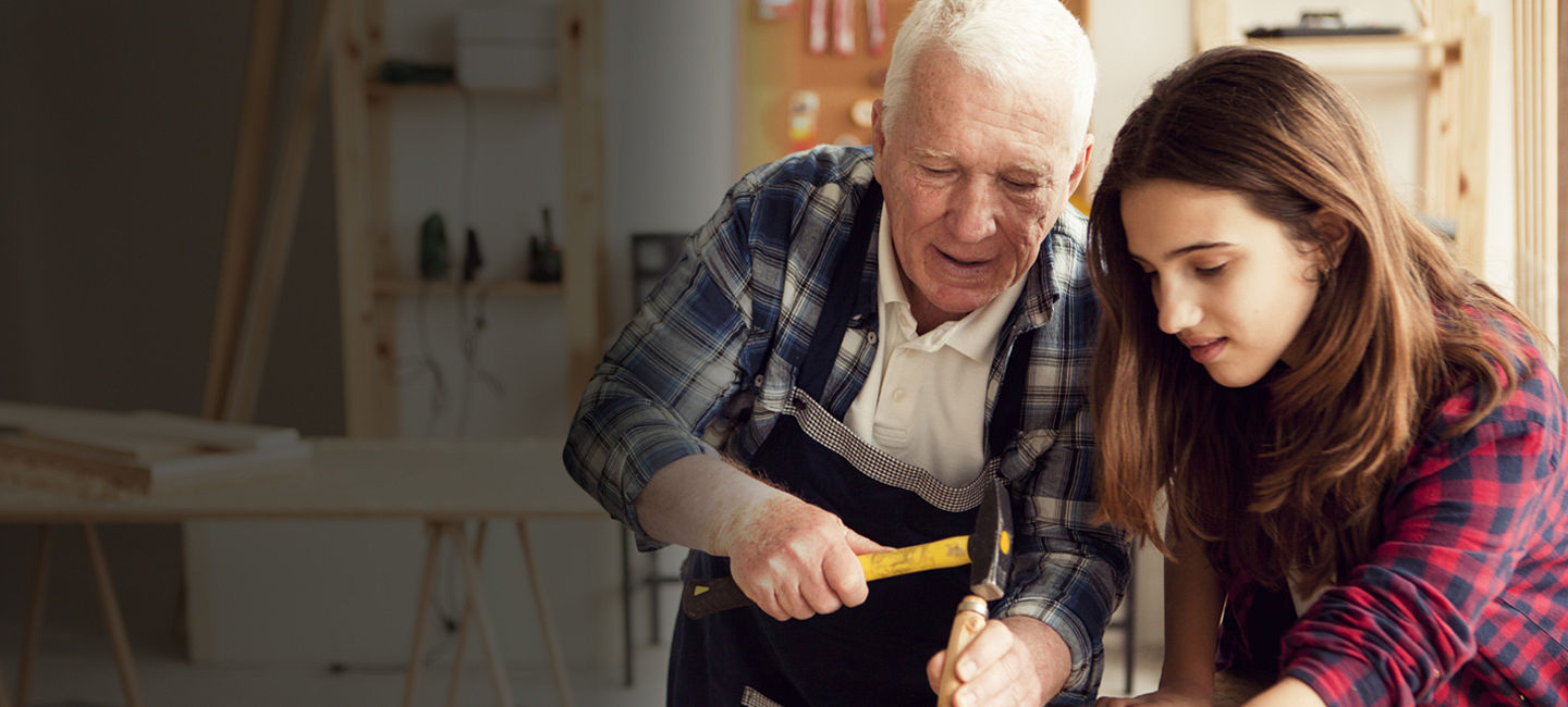 Grandfather and granddaughter woodworking together