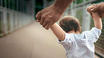 Small child getting help learning to walk from a parent.