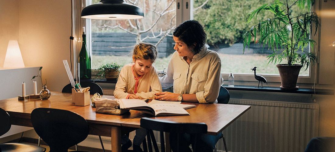 Mother and daughter doing homework at their kitchen table.