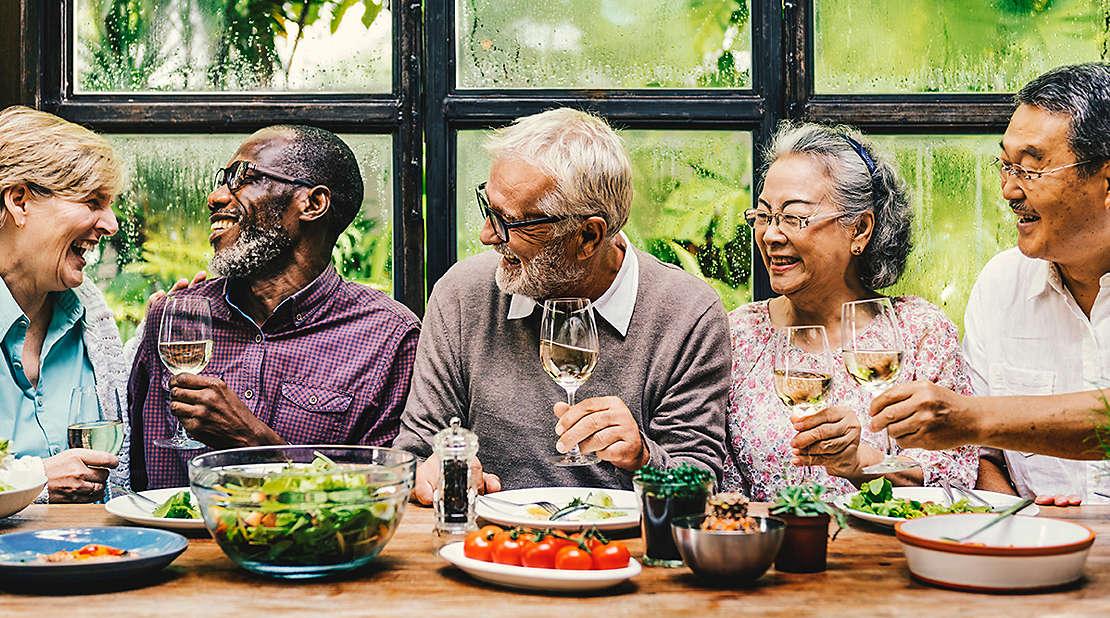 Five older friends toasting wine glasses.
