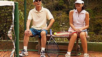 Older couple playing tennis