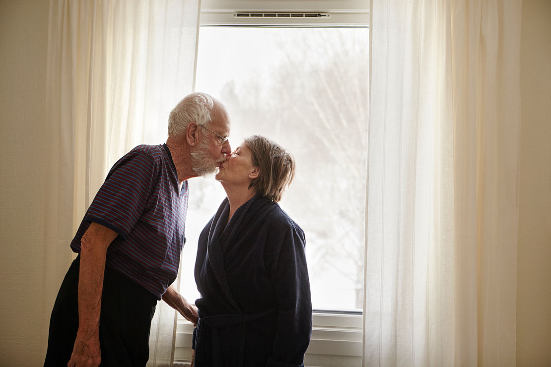 Senior couple kissing next to window