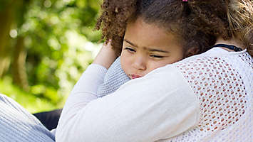 Small girl being hugged by her mom