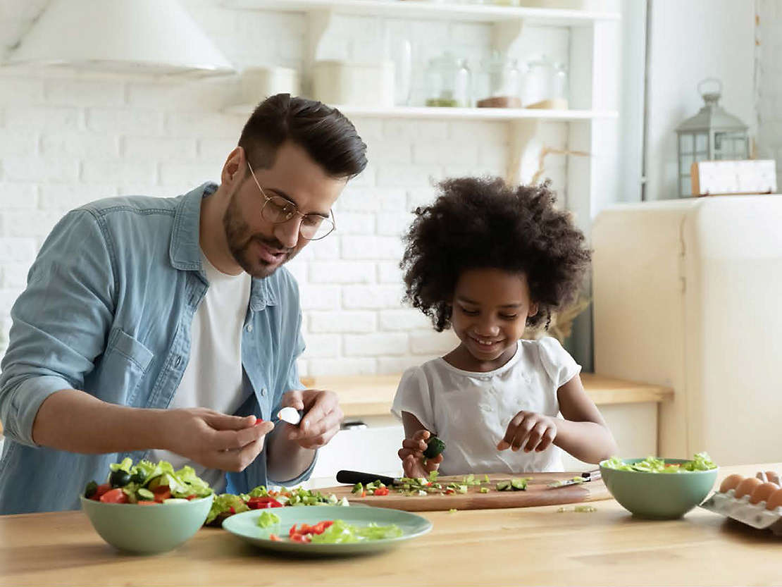 Father and daughter making salad in their kitchen