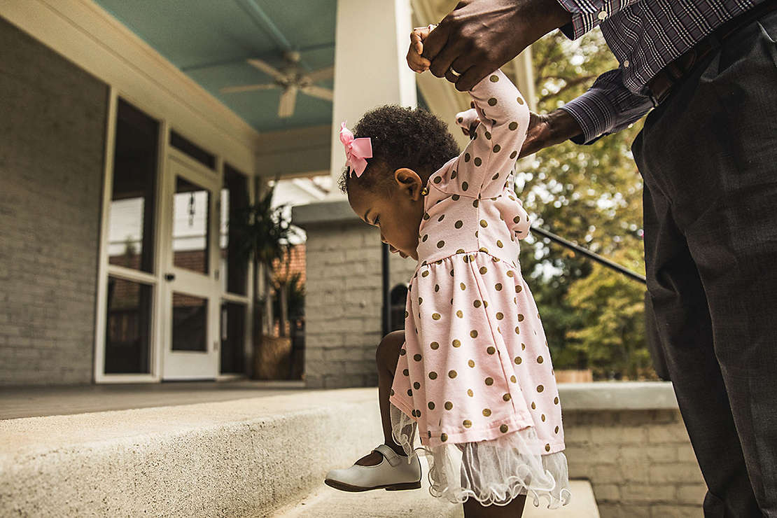 Father and daughter (18 months) walking up steps to house