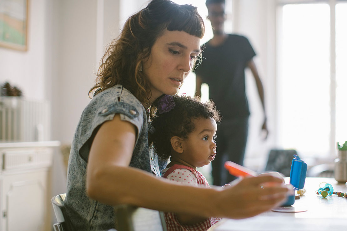 Woman working while sitting with daughter at table in house
