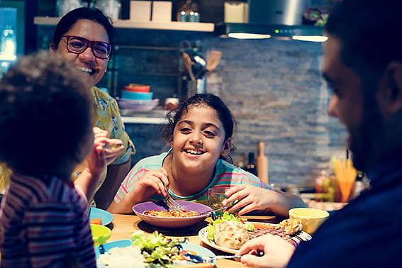 Family eats and laughs around kitchen table