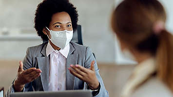 An agent wearing a mask talking with a client.