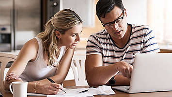 Couple looking at paper work and a computer.