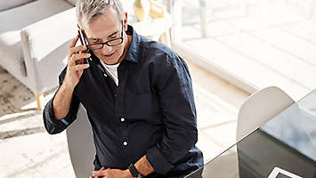 A mature man on the phone and working on his computer.