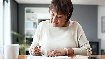 A mature woman sitting at a table with a calculator writing on papers.