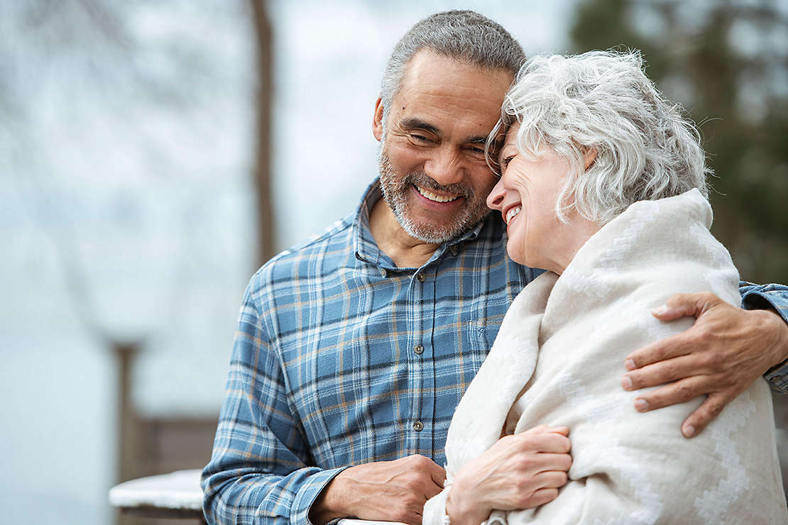 An older couple embracing and smiling on a park bench.