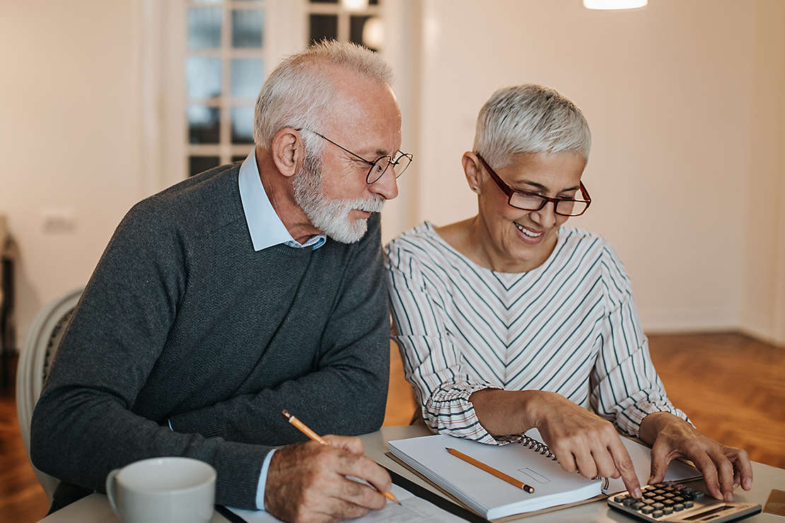Older couple reviewing their finances at their kitchen table.