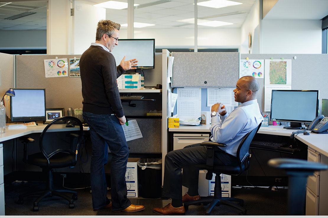 Co-workers talking in an office.