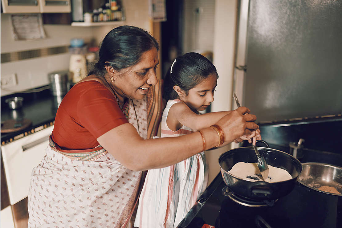 Grandmother cooking with granddaughter.