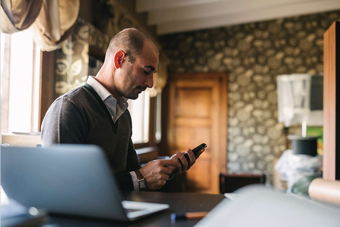 Businessman using a phone in home office