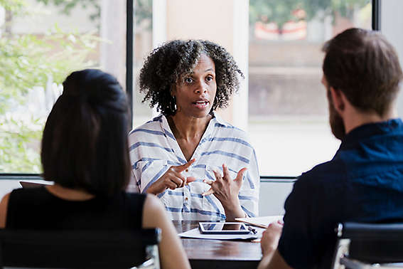 Serious female financial advisor talks with couple