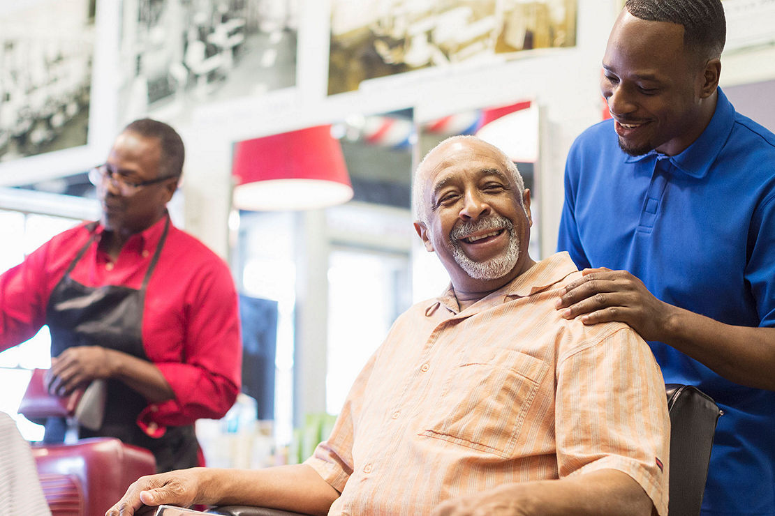 Barber talking to customer in his barbershop