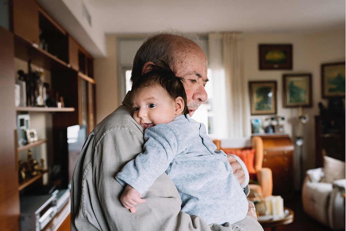 Grandfather holding young grandchild.