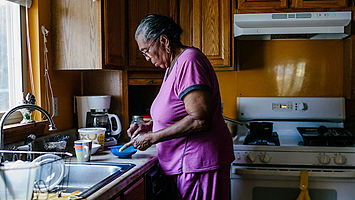 Elderly women in kitchen cooking