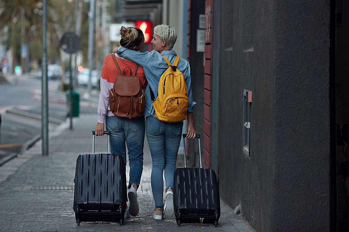 Two girlfriends walking down city street with luggage
