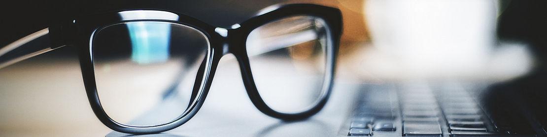 Black eye glasses on top of a desk.