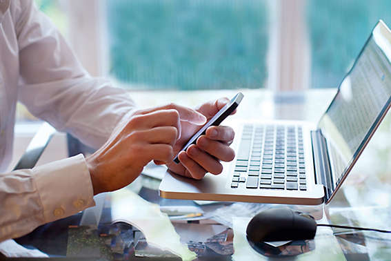 Man sitting at work desk on the phone