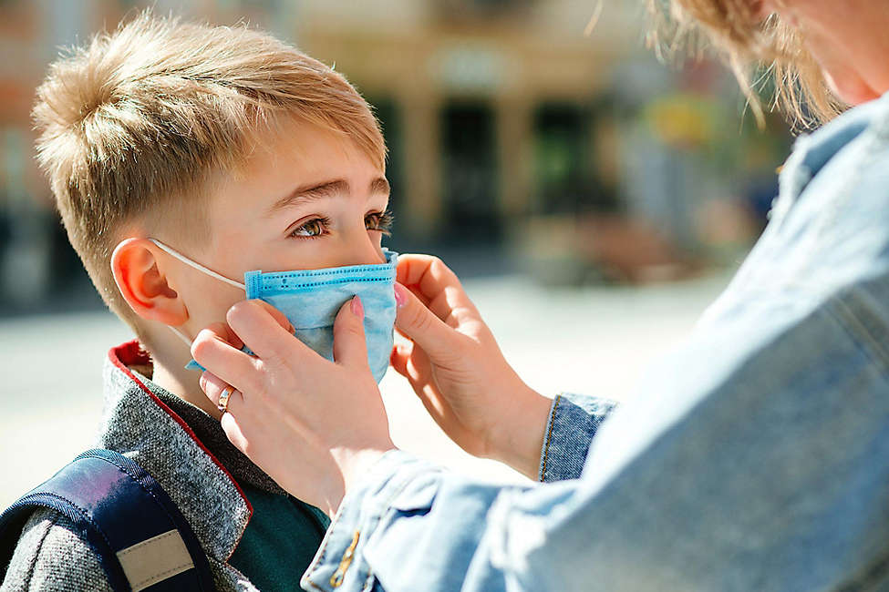 Mother covering son with face mask