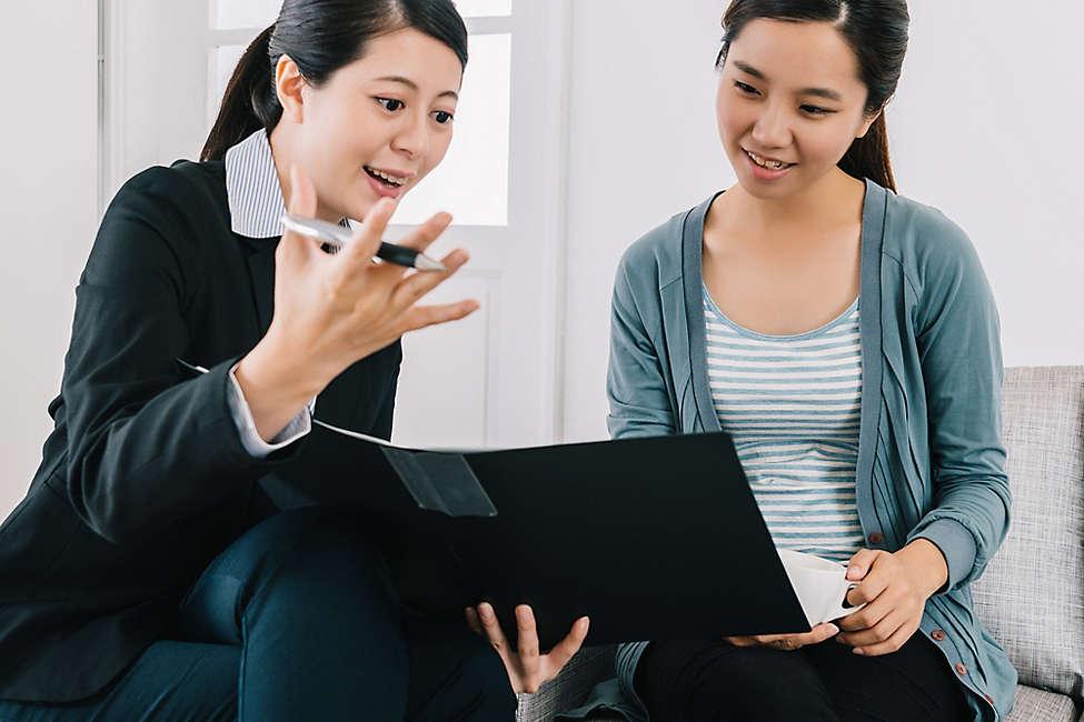 Chinese women going over portfolio