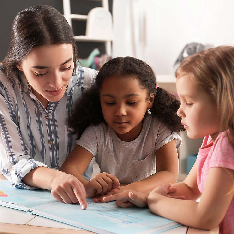 Woman and two young girls reading