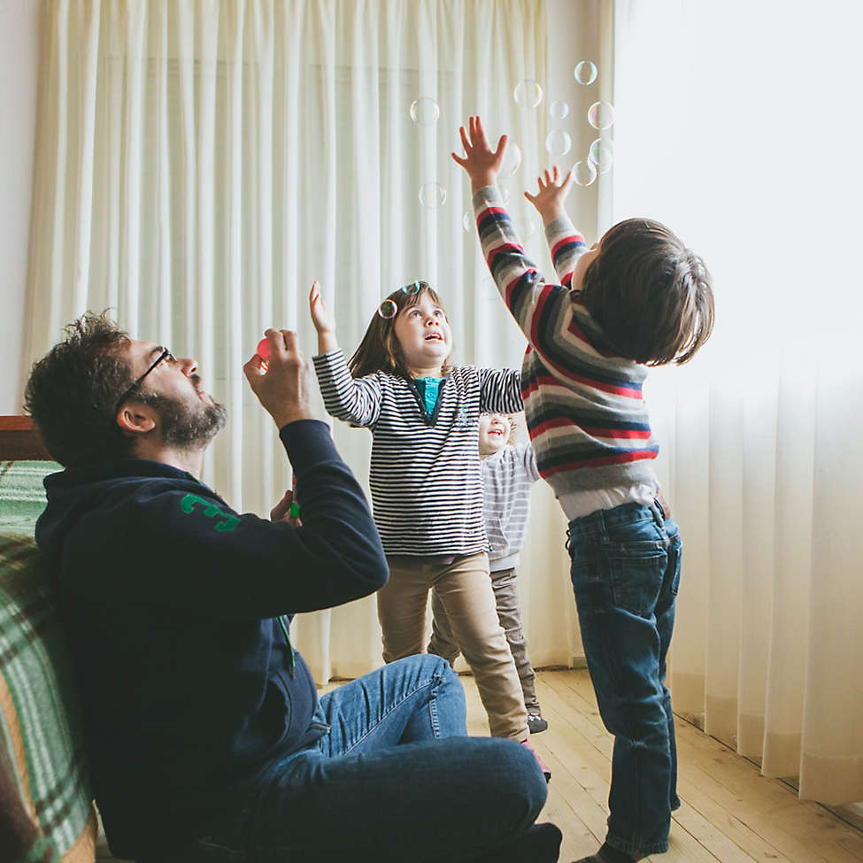 Father blowing bubbles with kids