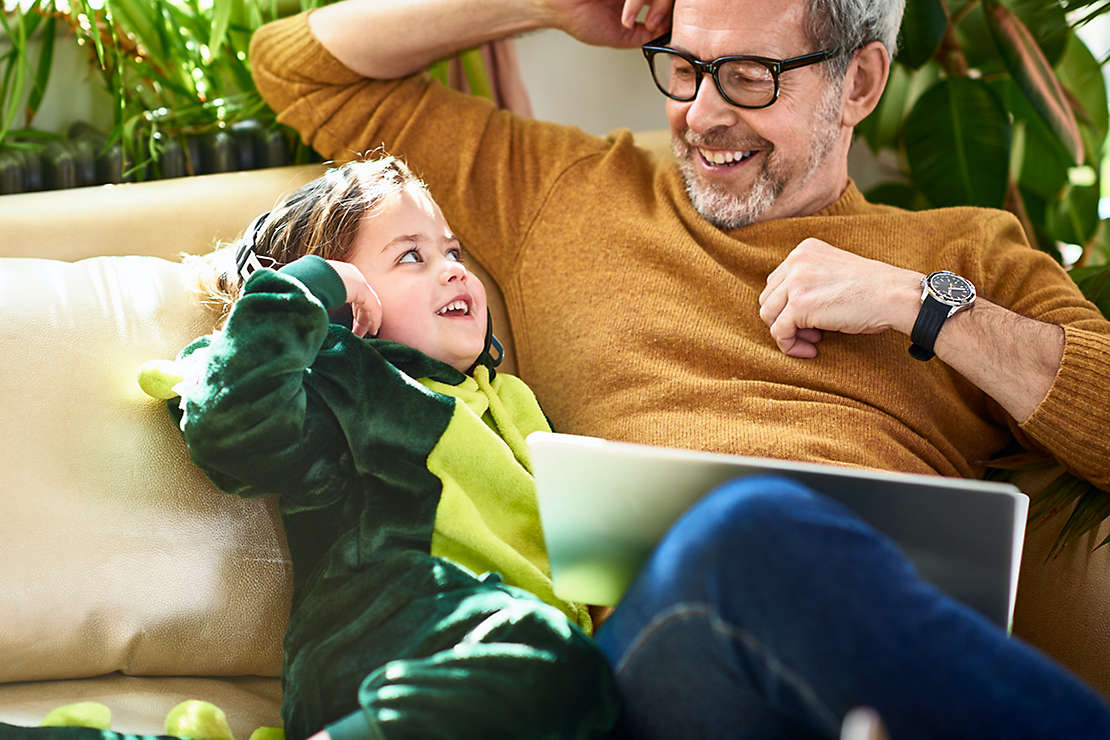 Father and daughter relaxing on couch