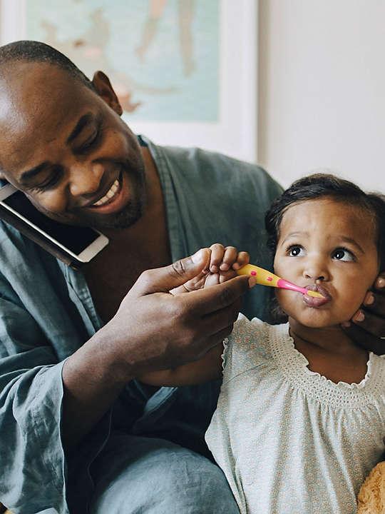 Dad brushing daughters teeth