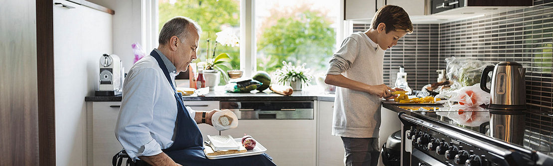 Middle-aged gentleman and son cooking together in kitchen