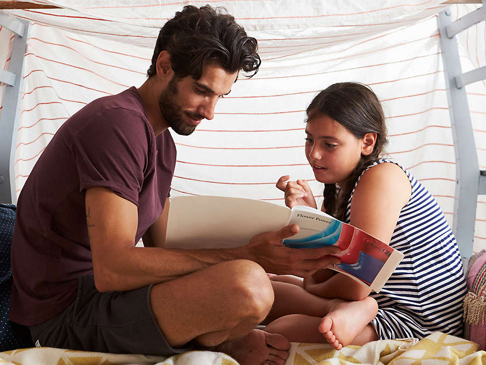 Father and daughter reading in a fort
