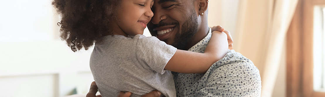 Father hugging young daughter