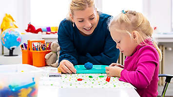Teacher doing crafts with young girl