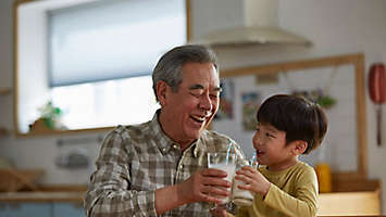 Grandfather and Grandson drinking milk together in their kitchen.