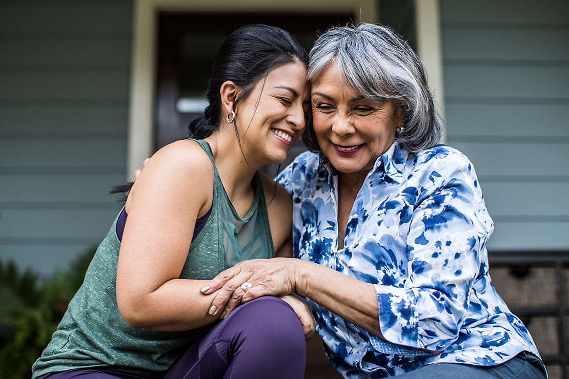 Mother and Daughter hugging on porch