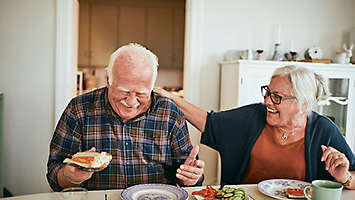A mature couple at the table laughing and eating a meal.