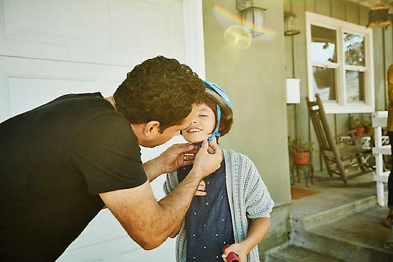 Father putting a bike helmet on his child.