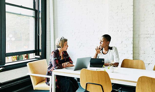 businesswomen-leaning-on-table
